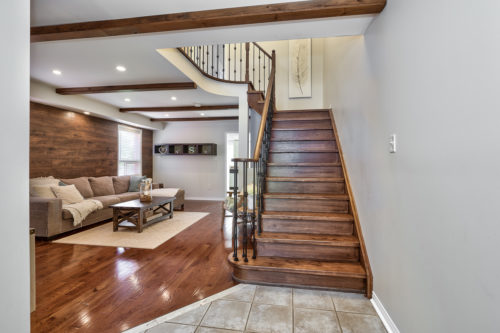 Oak Staircase with Metal Pickets Leads to Upper Level